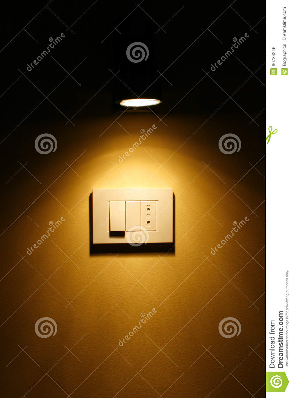 Spotlight above dark yellow wall outlet and switch