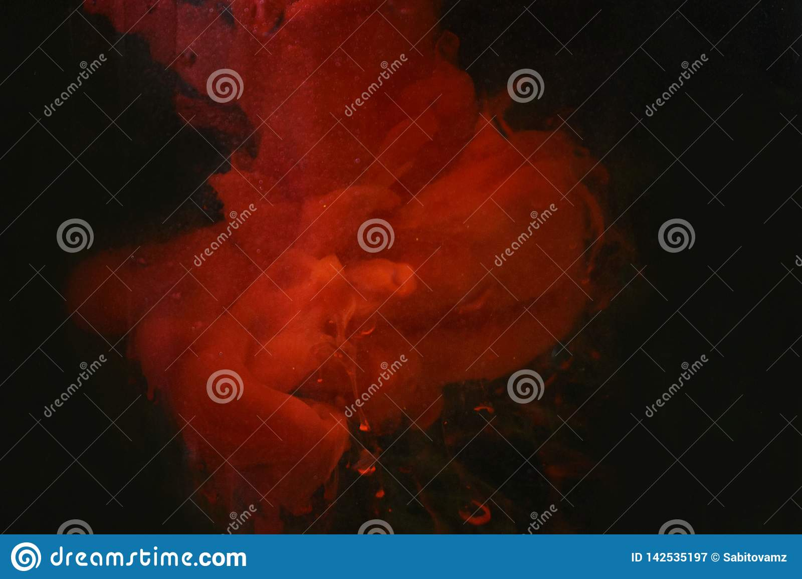 Spots of red paint in water dark background texture closeup macro