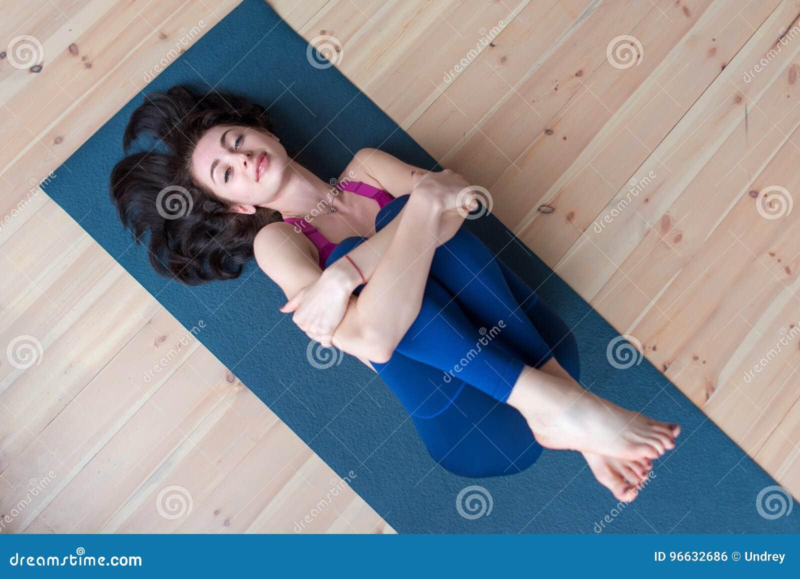 Spotswoman relaxado consideravelmente de sorriso com o cabelo marrom bonito que encontra-se na esteira que abraça seus pés que ol