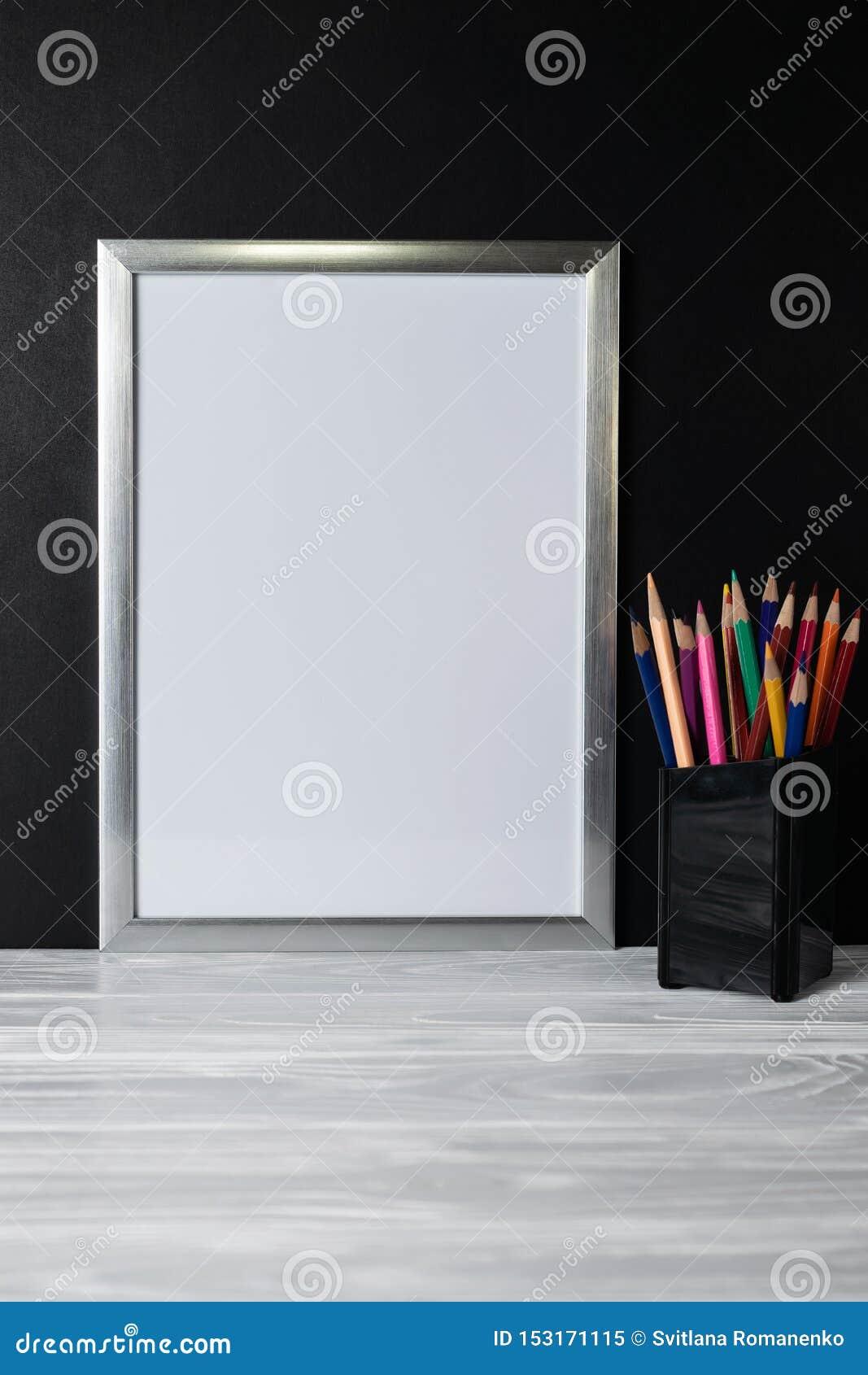 Spott herauf weißen Rahmen und farbige Bleistifte auf hölzernem Regal und Tafel