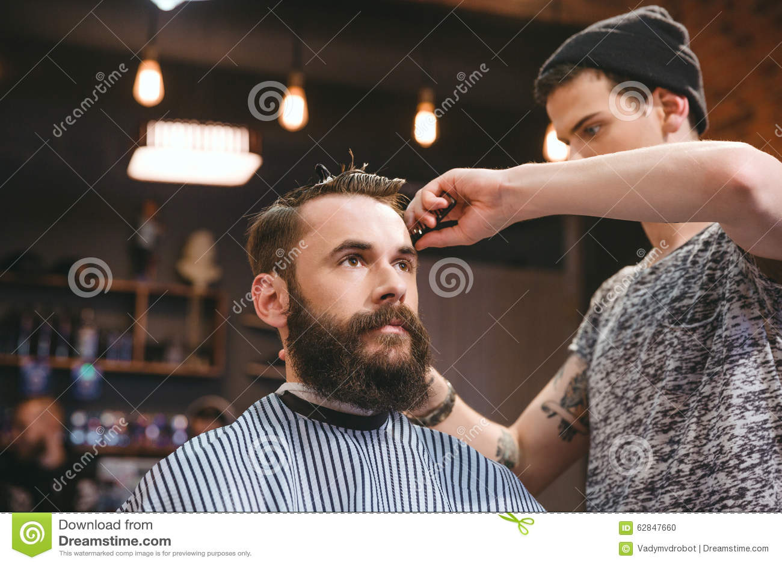 Sprawnego fryzjera męskiego tnący włosy młody człowiek z brodą