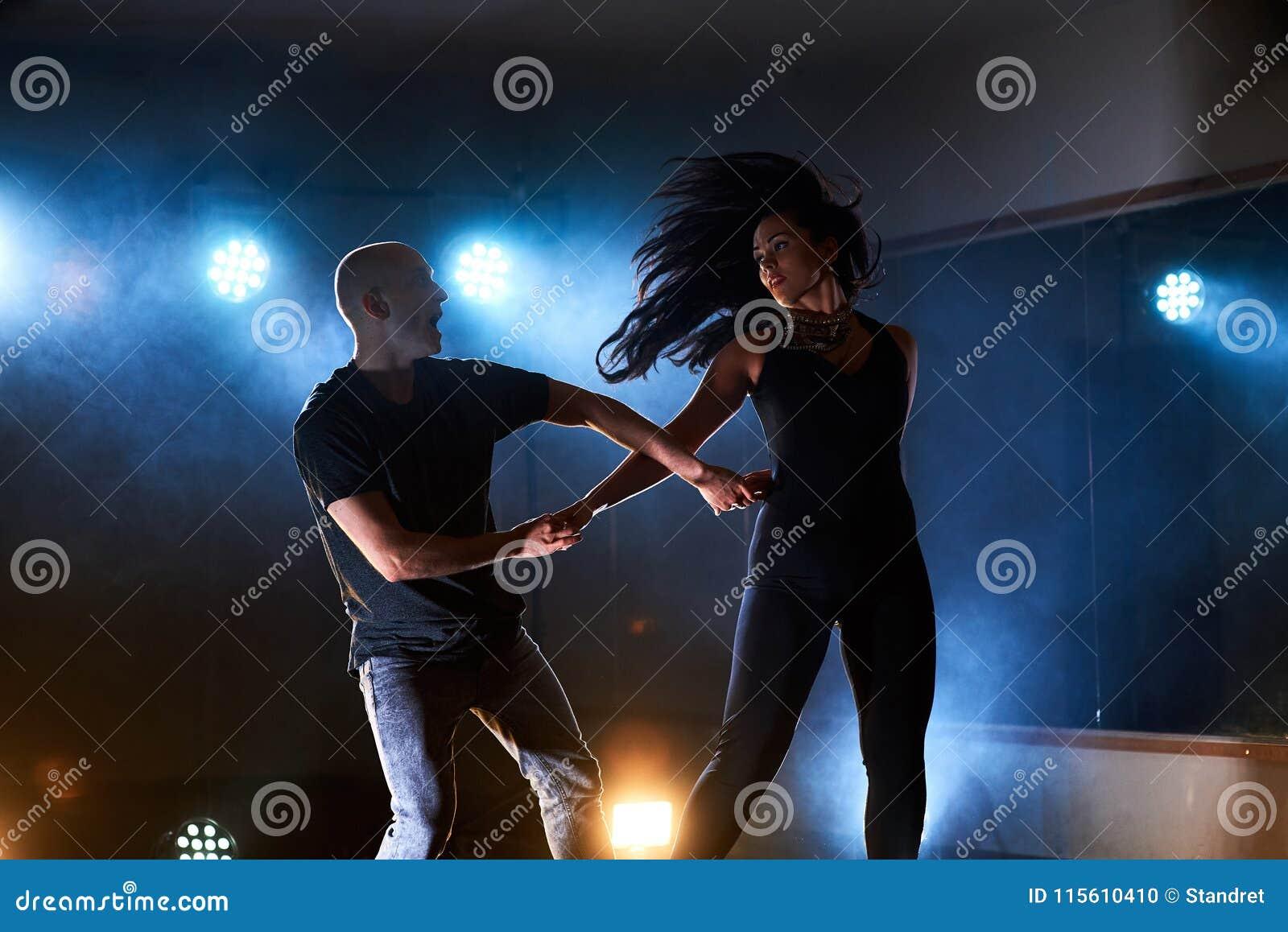 Sprawni tancerze wykonuje w ciemnym pokoju pod porozumiewają się światło i dymią Zmysłowa para wykonuje artystycznego