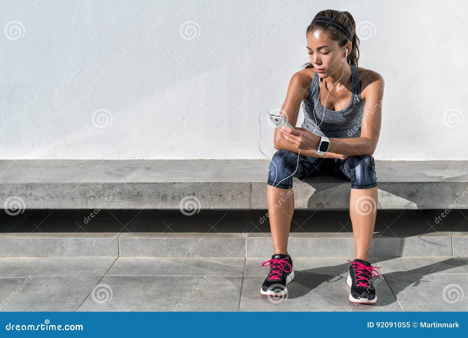 Sprawność fizyczna biegacza dziewczyna używa muzycznego telefon komórkowego app