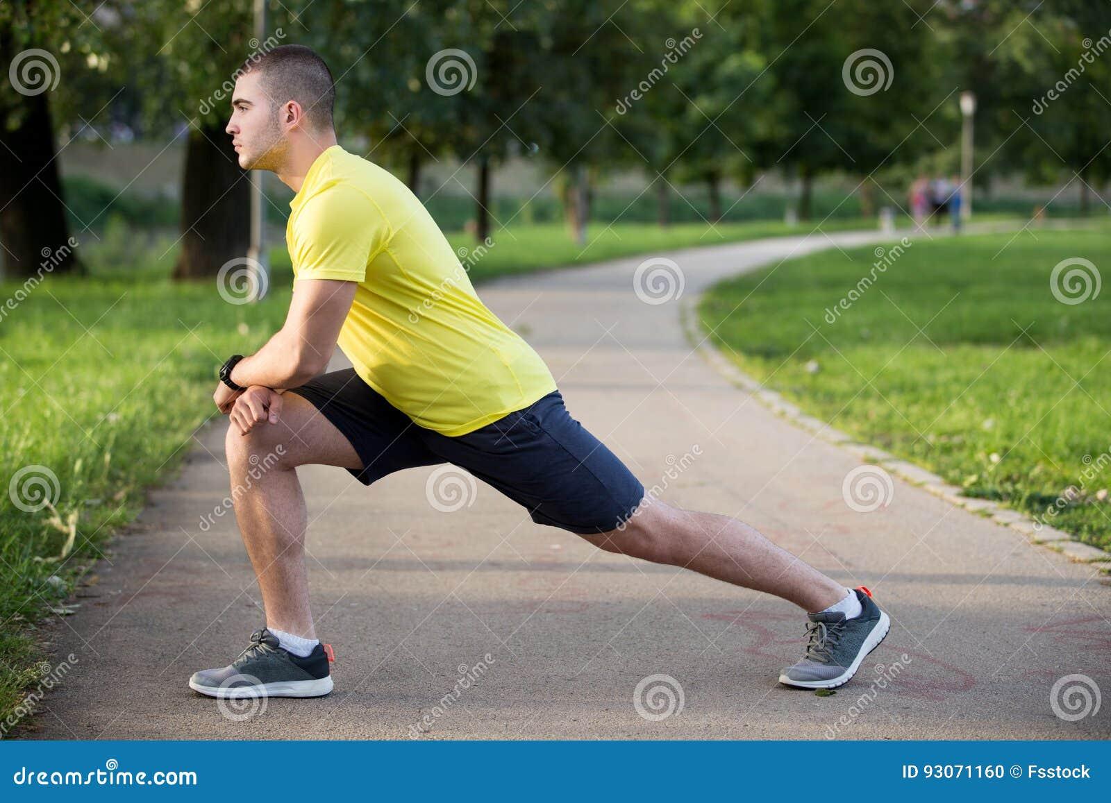 Sprawność fizyczna mężczyzna rozciągania ręki ramię przed plenerowym treningiem Sporty męska atleta w miastowy parkowy rozgrzewko