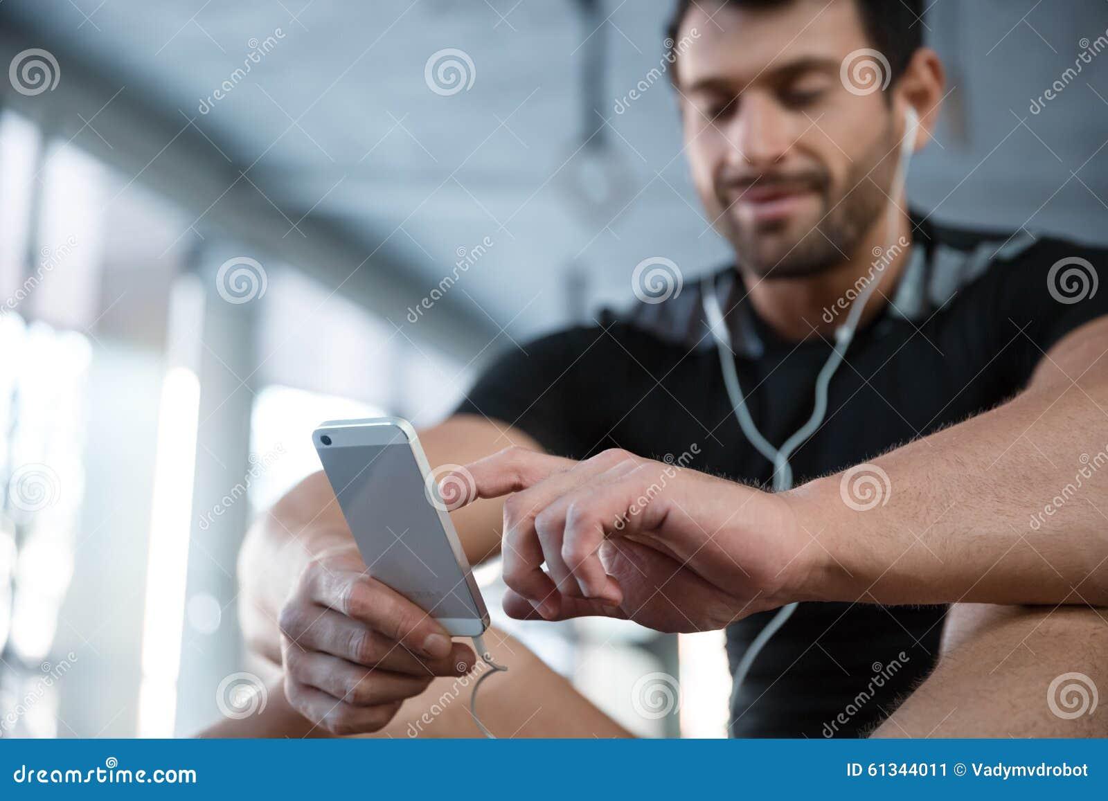 Sprawność fizyczna mężczyzna używa smartphone w gym