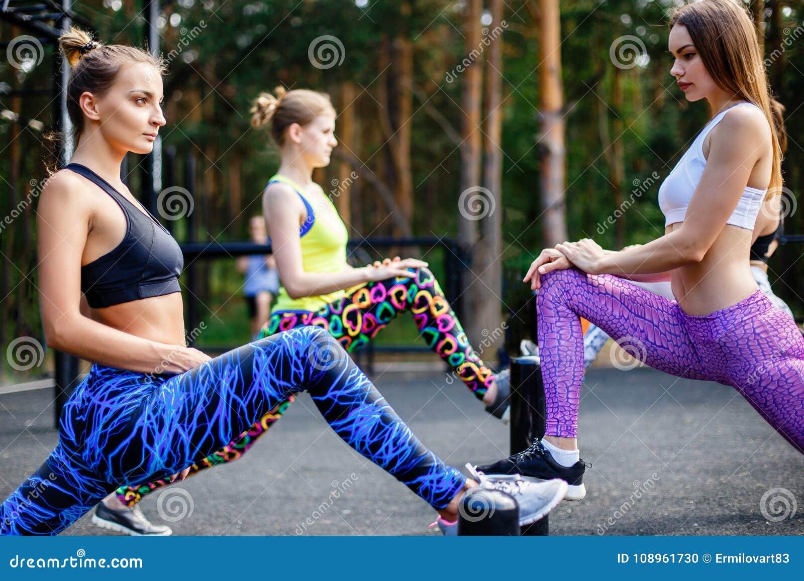 Sprawność fizyczna, sport, przyjaźń i zdrowy stylu życia pojęcie, - grupa atrakcyjne młode kobiety robi lunge outdoors