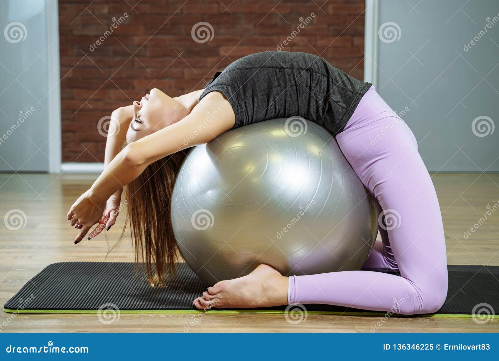Sprawność fizyczna, sport, styl życia - młoda kobieta robi ćwiczeniom z dysponowaną piłką w pilates klasie