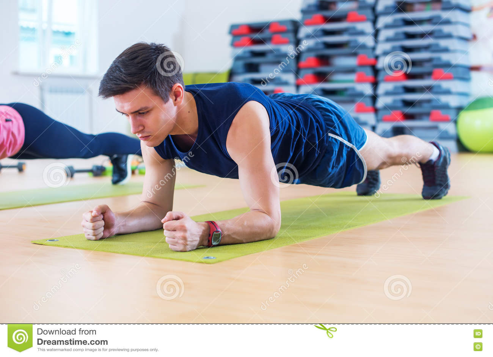Sprawność fizyczna trenuje sportowego sporty mężczyzna robi deski ćwiczeniu w gym lub joga grupujemy ćwiczyć trening