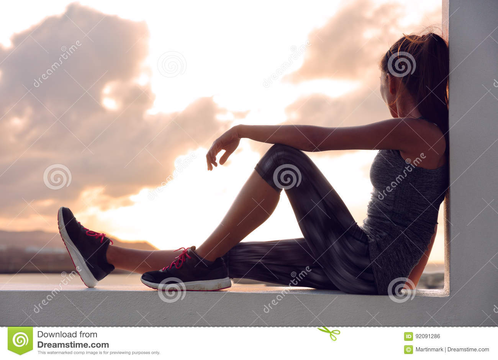 Sprawności fizycznej atlety biegacza kobieta relaksuje w zmierzchu