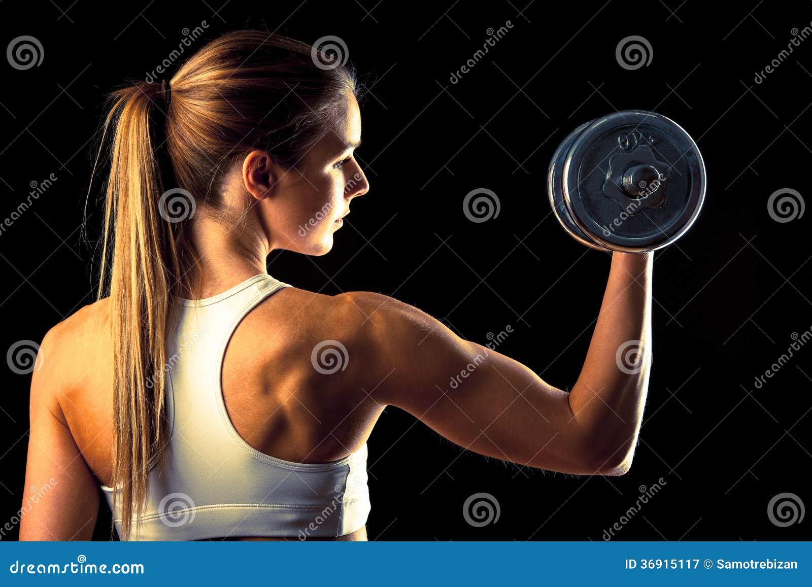 Sprawności fizycznej dziewczyna - atrakcyjna młoda kobieta pracująca z dumbbells out