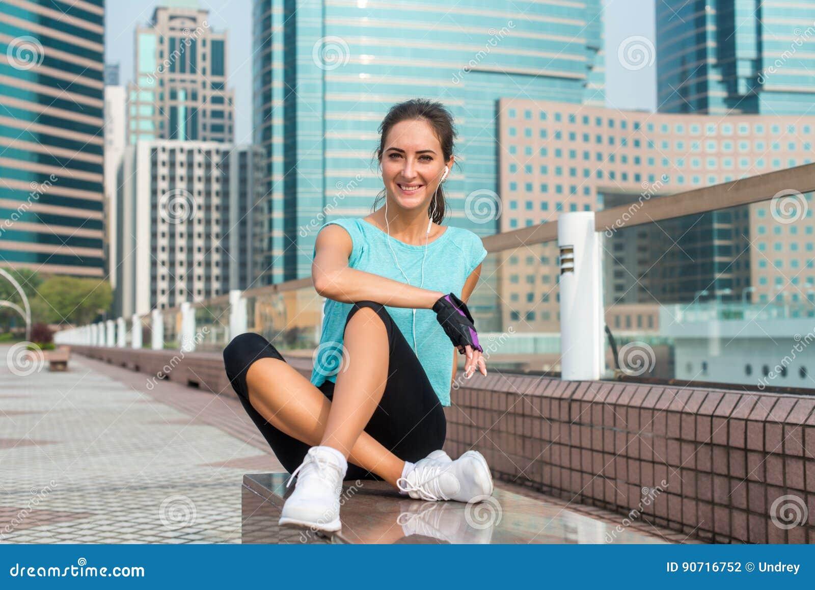 Sprawności fizycznej dziewczyna relaksuje po treningu sesyjnego obsiadania na ławce w miasto alei Młoda sportowa kobieta bierze p