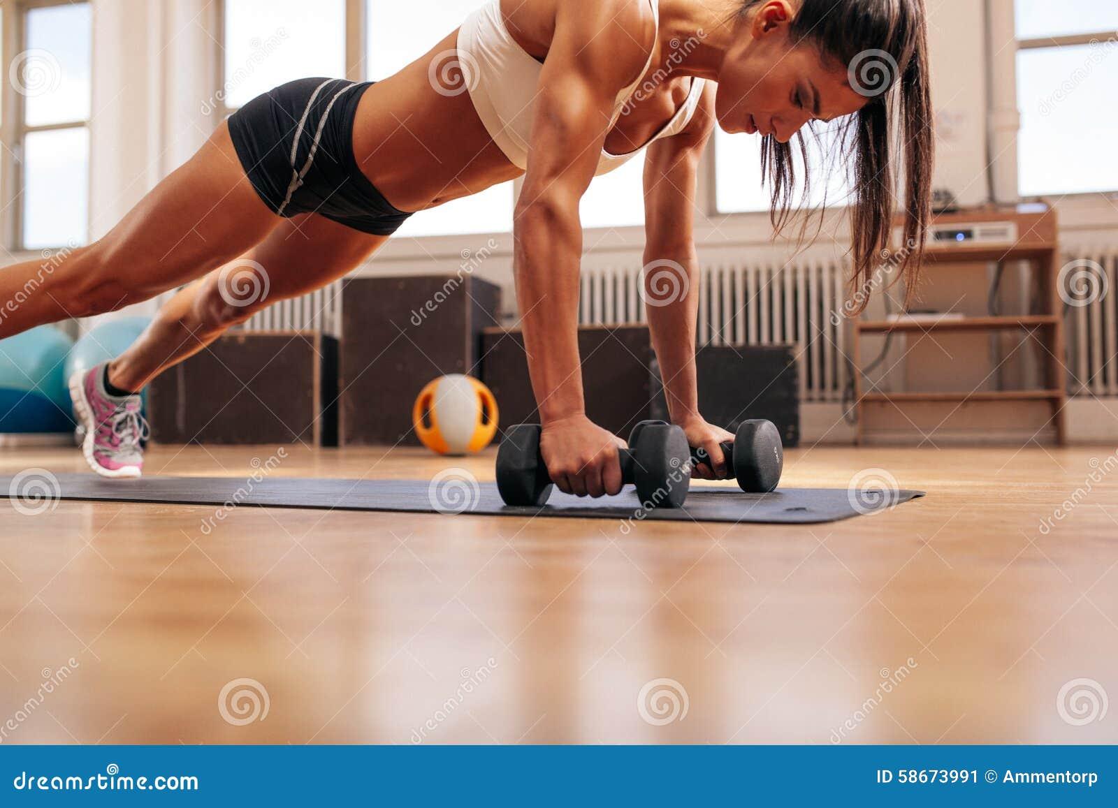 Sprawności fizycznej kobieta podnosi ćwiczenie z dumbbells robić pcha