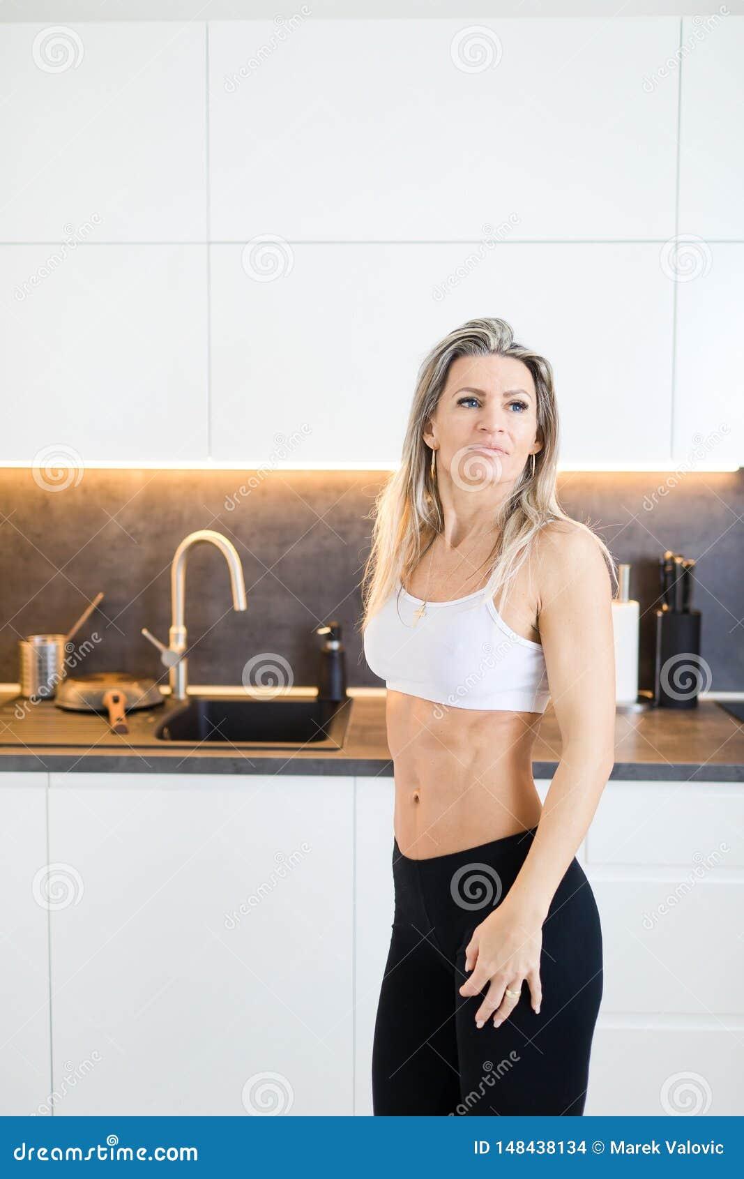 Sprawności fizycznej kobieta w kuchni - treningu ciało