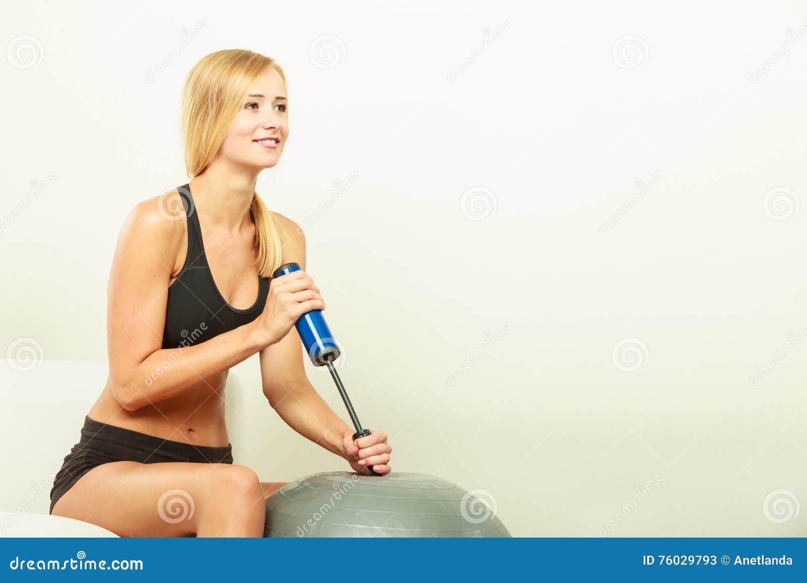 Sprawności fizycznej kobieta z lotniczej pompy pompowania dysponowaną piłką