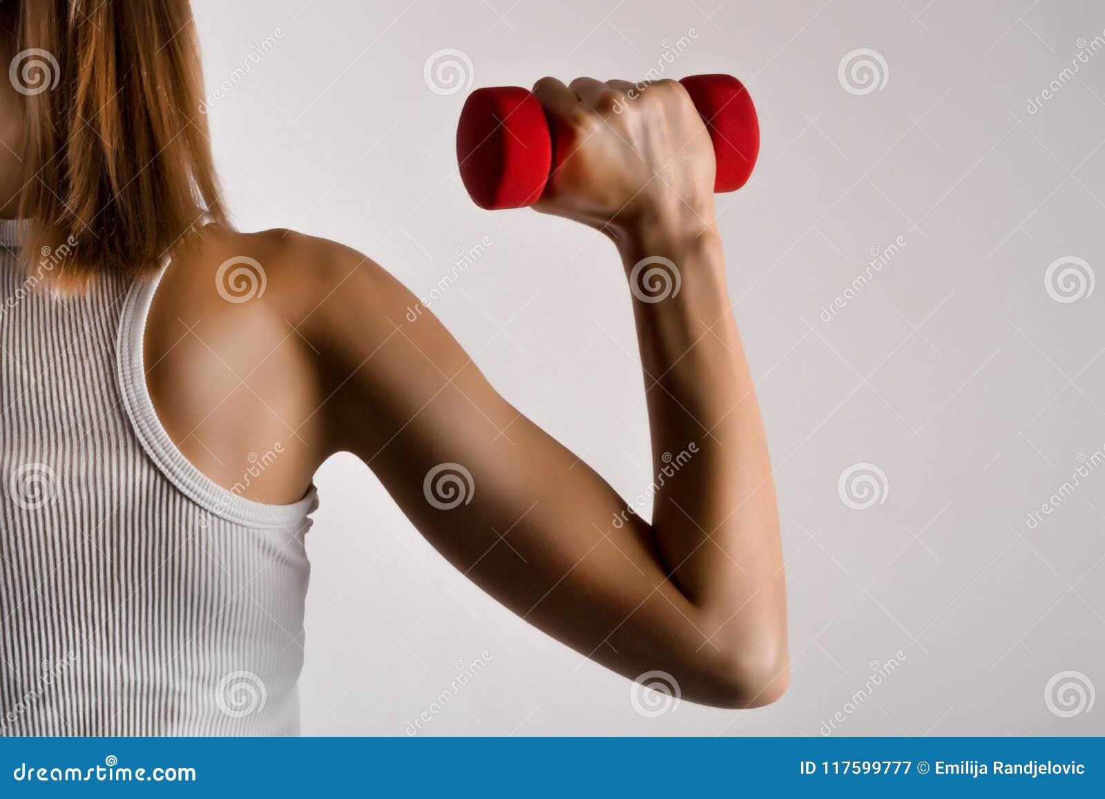 Sprawności fizycznej kobiety wzorcowa ręka z żółtym dumbbell na szarym pracownianym tle