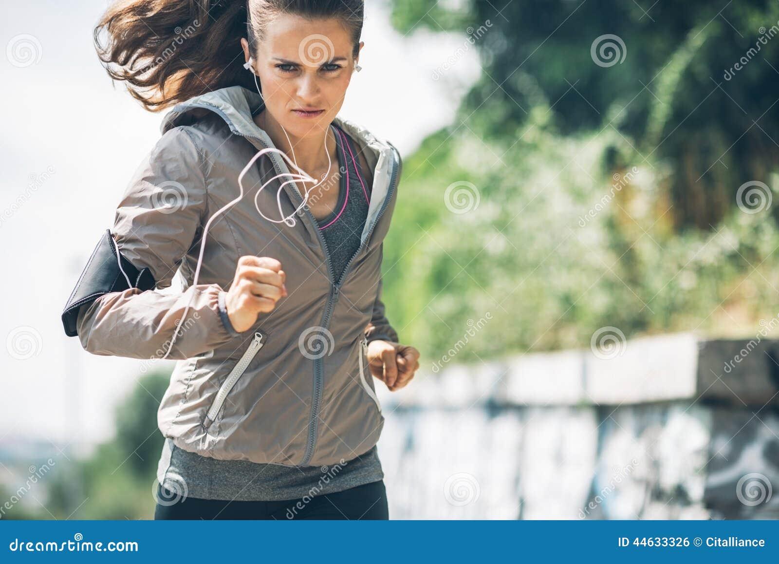 Sprawności fizycznej młoda kobieta jogging w miasto parku