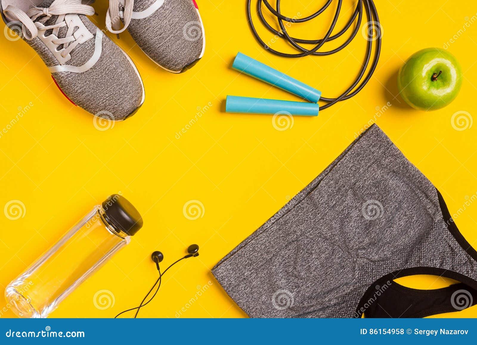 Sprawności fizycznych akcesoria na żółtym tle Sneakers, butelka woda, hełmofony i sporta wierzchołek,