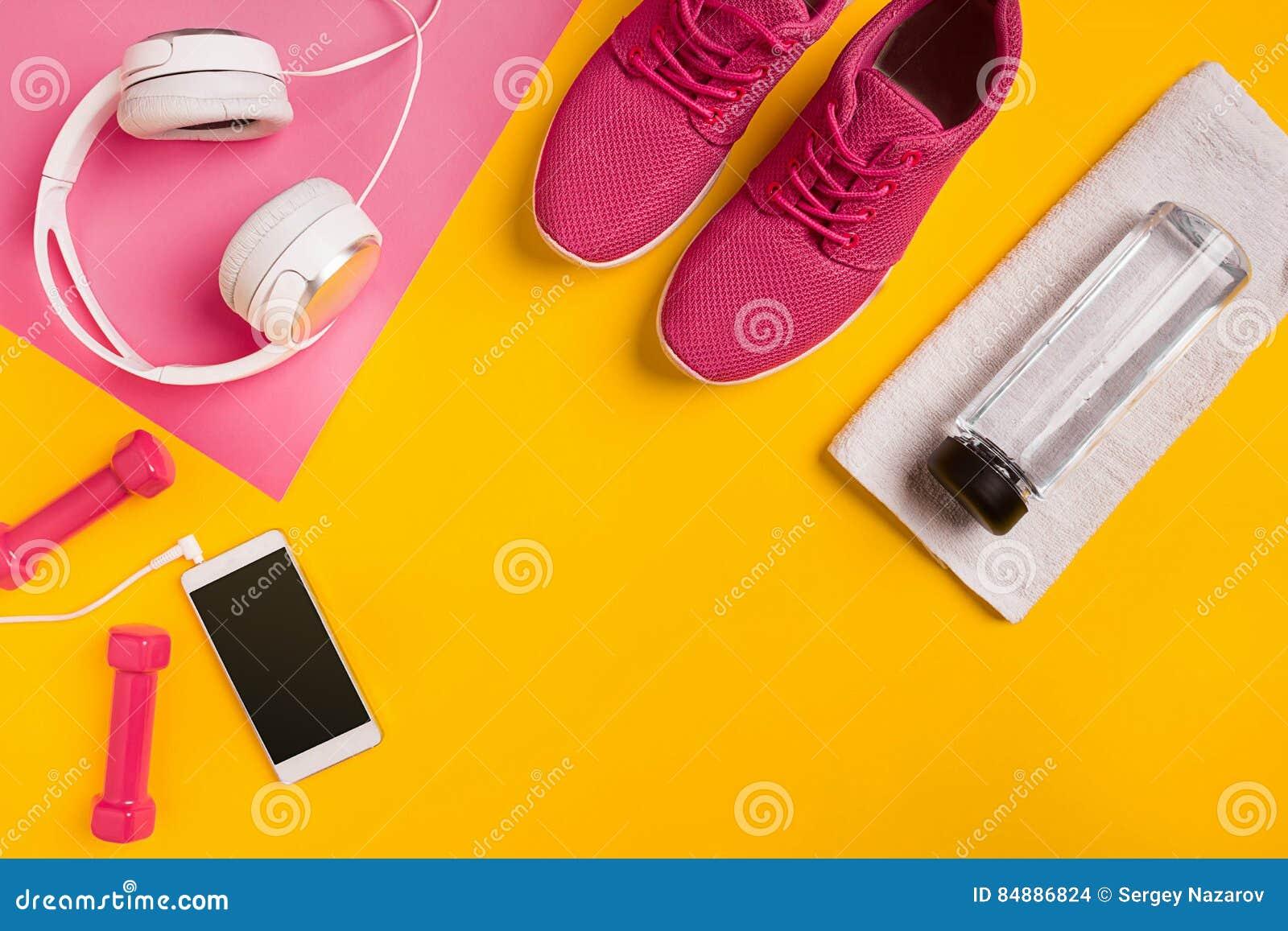Sprawności fizycznych akcesoria na żółtym tle Sneakers, butelka woda, słuchawki i dumbbells,