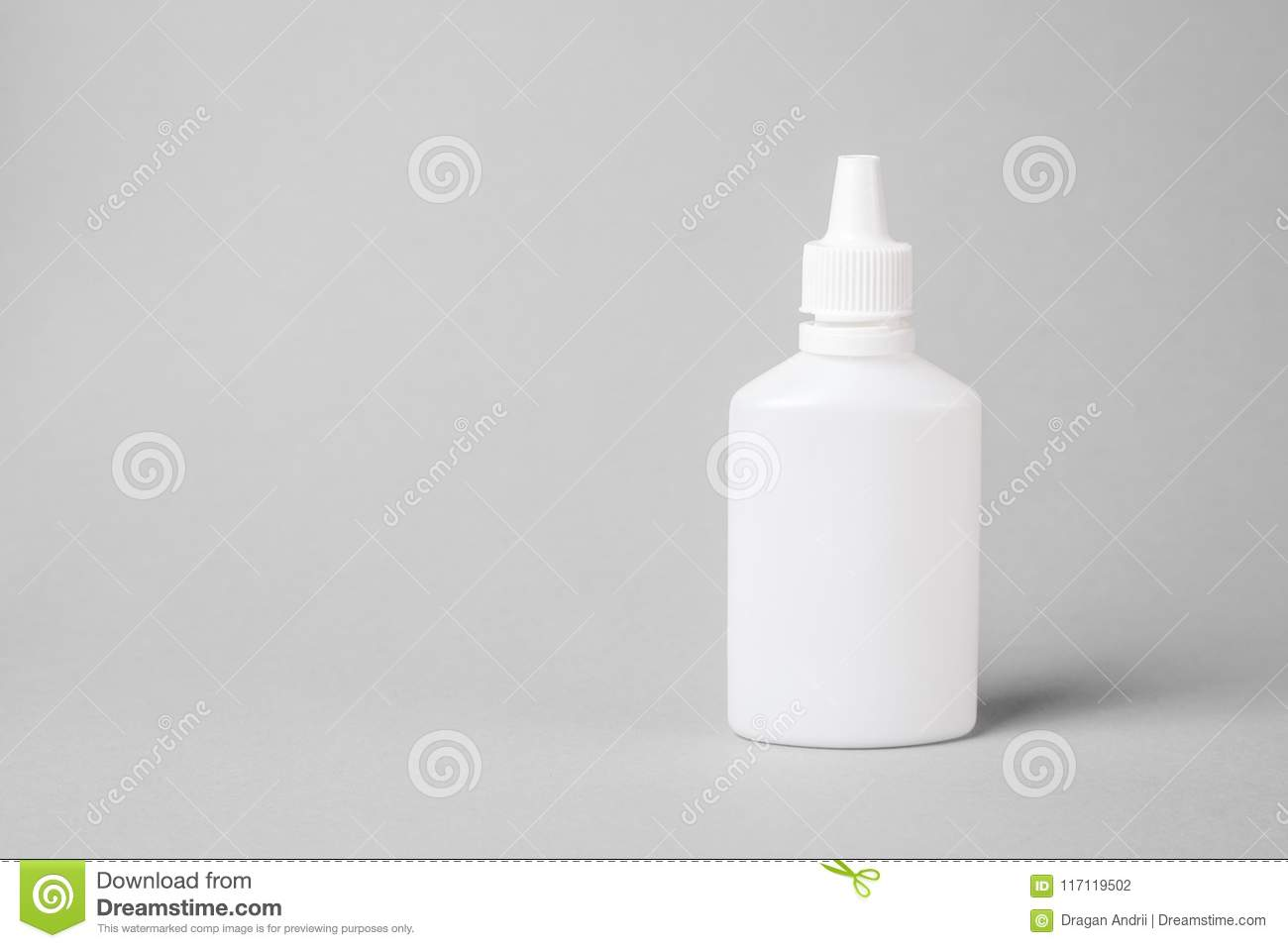 Spray for the nose in a white plastic bottle on a gray background. Aerosol from the common cold or allergy