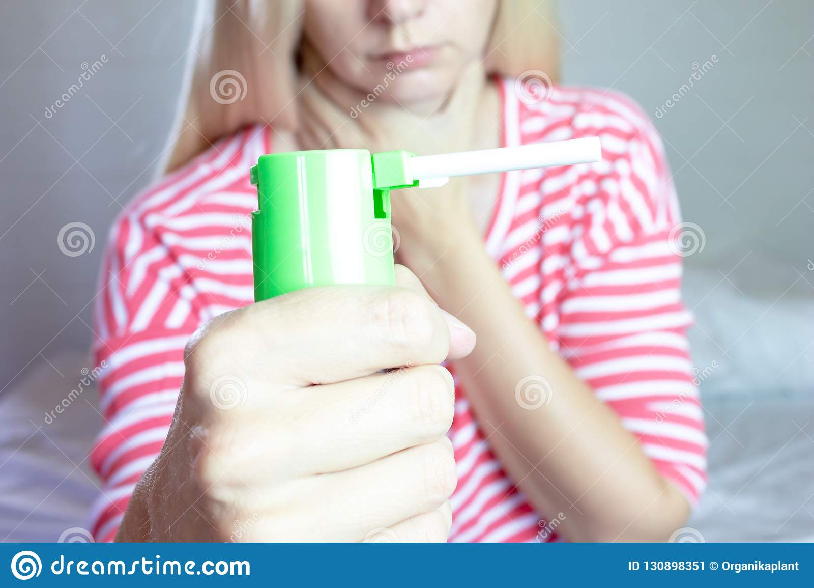 Spray for sore throat. Photo of a woman who holds spray in her hand. The concept of health and disease