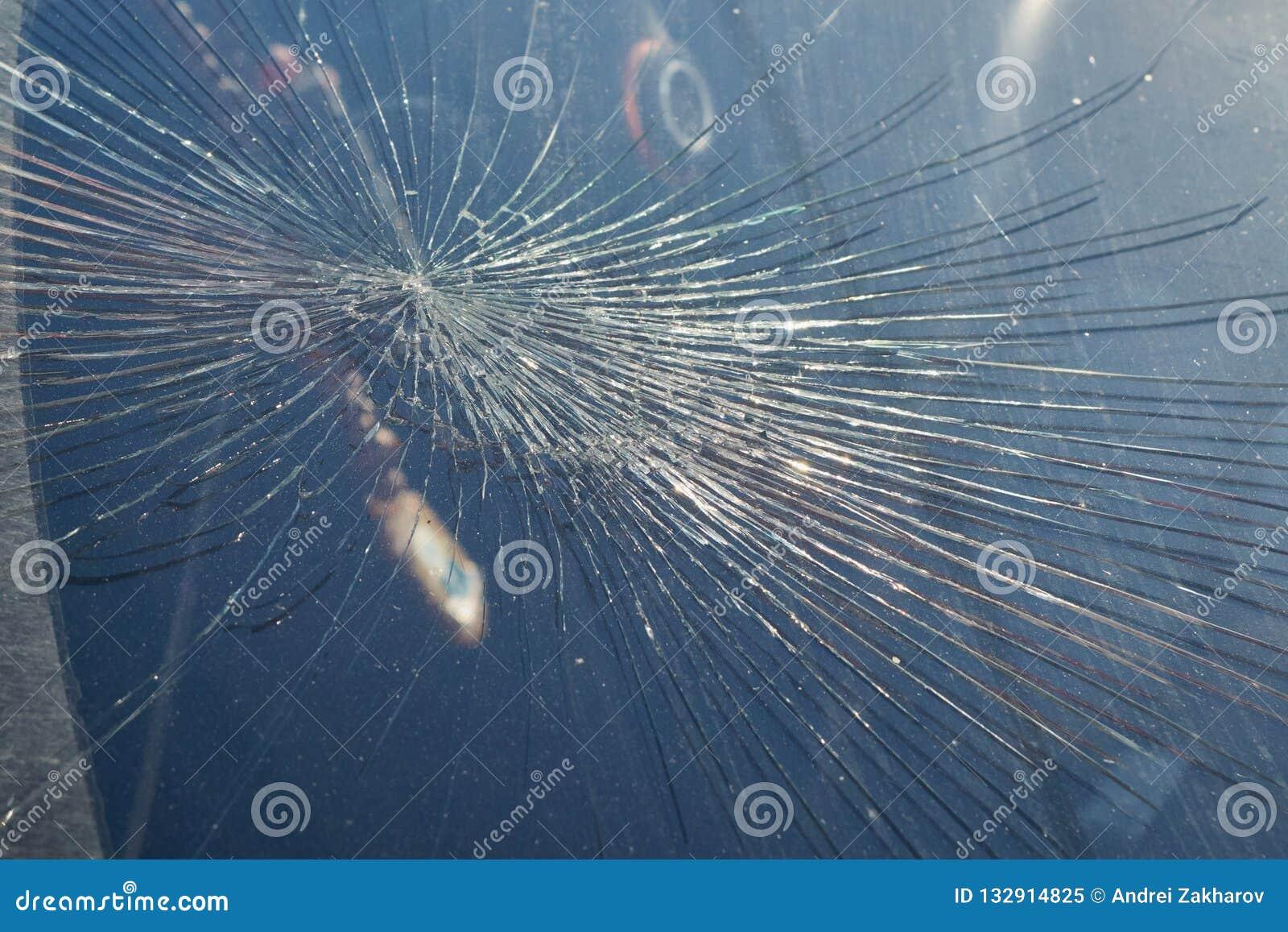 Sprickor från inverkan på vindrutan av bilen
