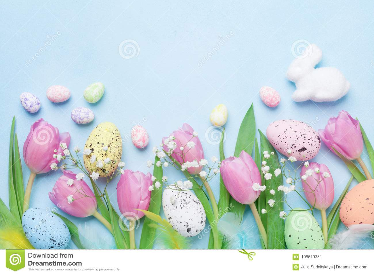Spring background with flowers, bunny, colorful eggs and feathers on blue table top view. Happy Easter card.