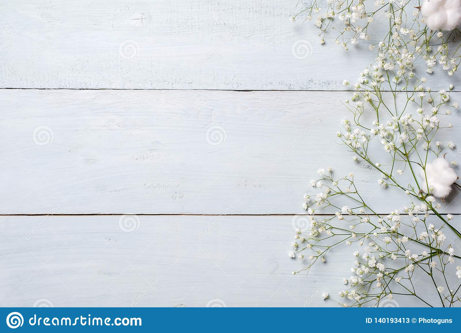 Spring background. White rustic flowers on blue wooden table. Banner mockup for womans or mother day, happy easter, spring holiday
