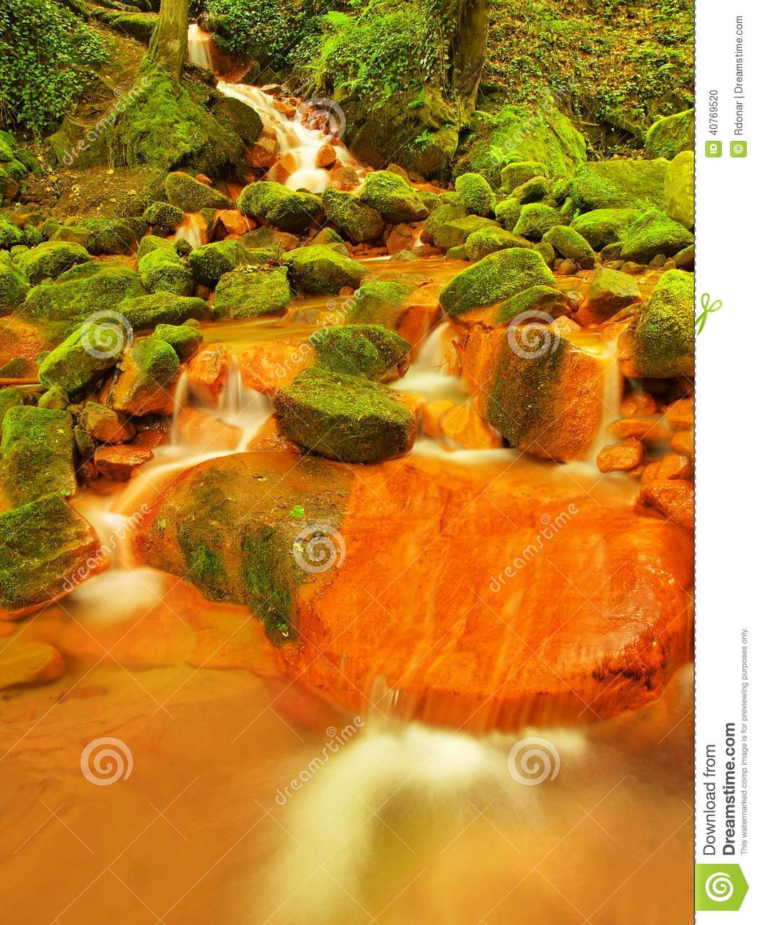 Spring cascades in rapid stream of mineral water. Red ferric sediments on big boulders