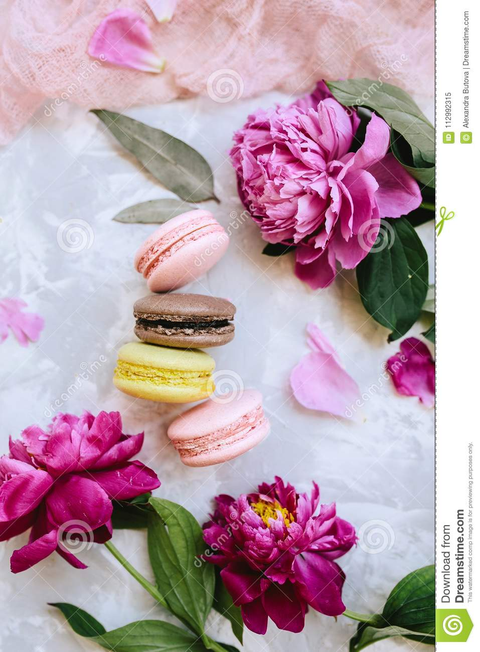 Spring composition flatlay: colorful macaroons with purple and pink peonies, green leaves on a light concrete background and a pin
