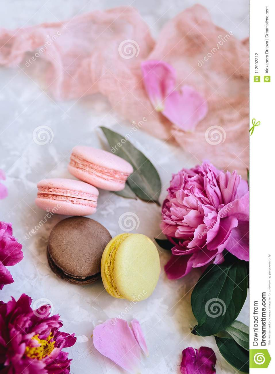 Spring composition: colorful macaroons with purple and pink peonies, green leaves on a light concrete background and a pink cloth