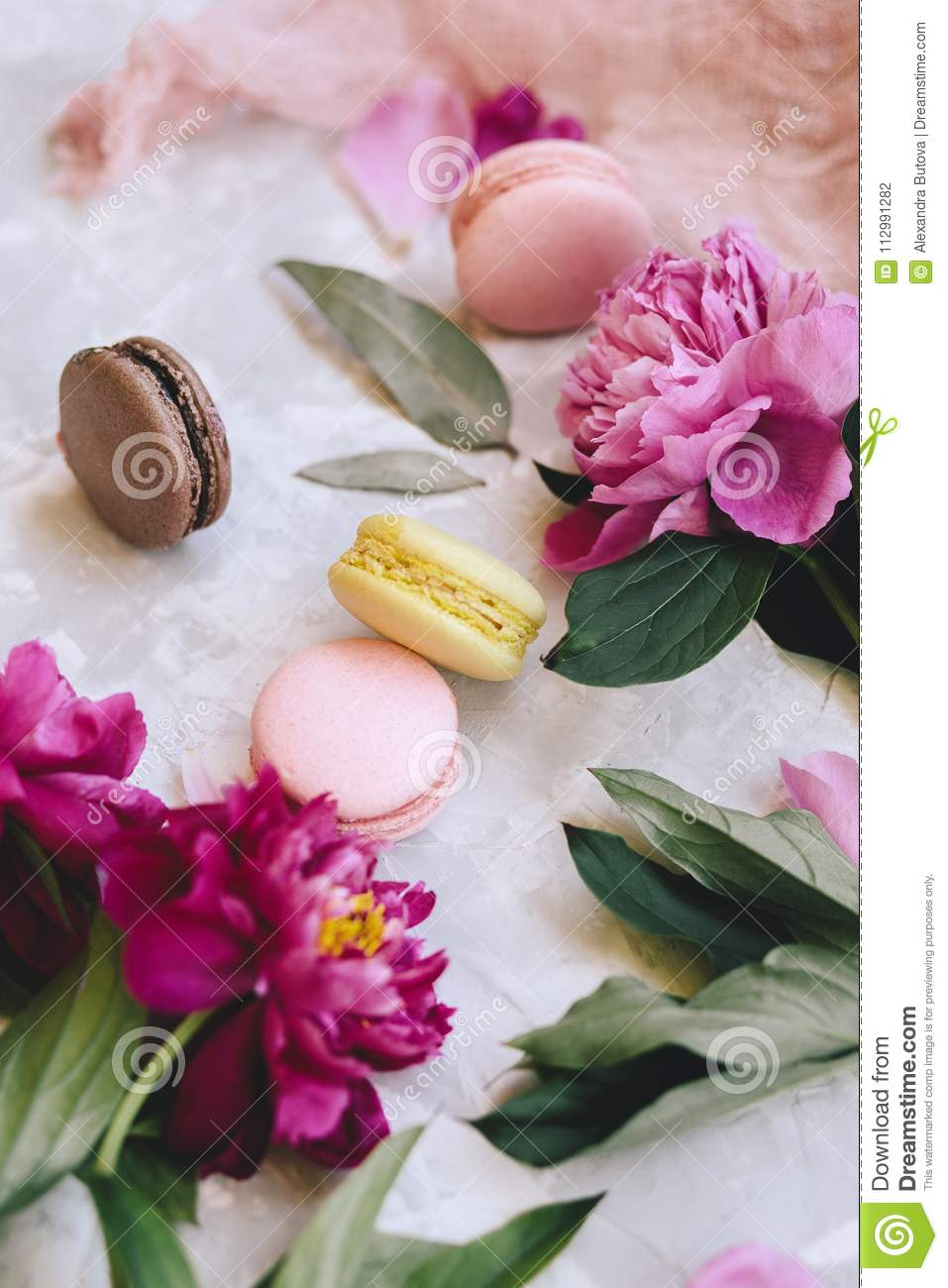Spring composition: colorful macaroons with purple and pink peonies, green leaves on a light concrete background