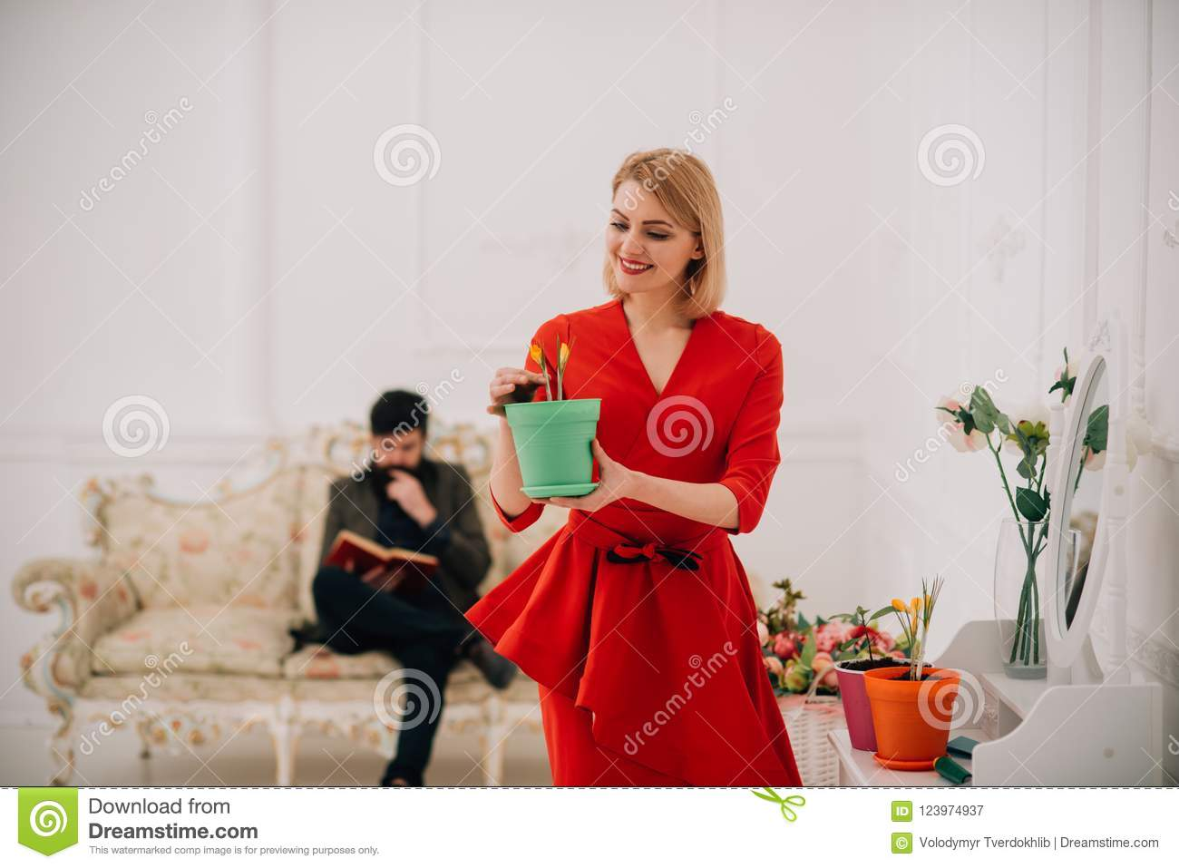 spring concept. sensual woman hold spring flower while man reading