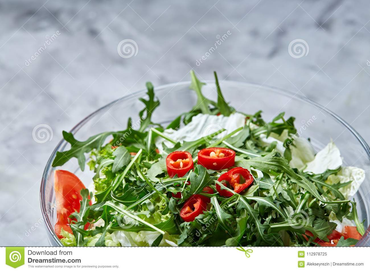Dietary mixed salad in glass sultana served with wooden spoon on white background, selective focus