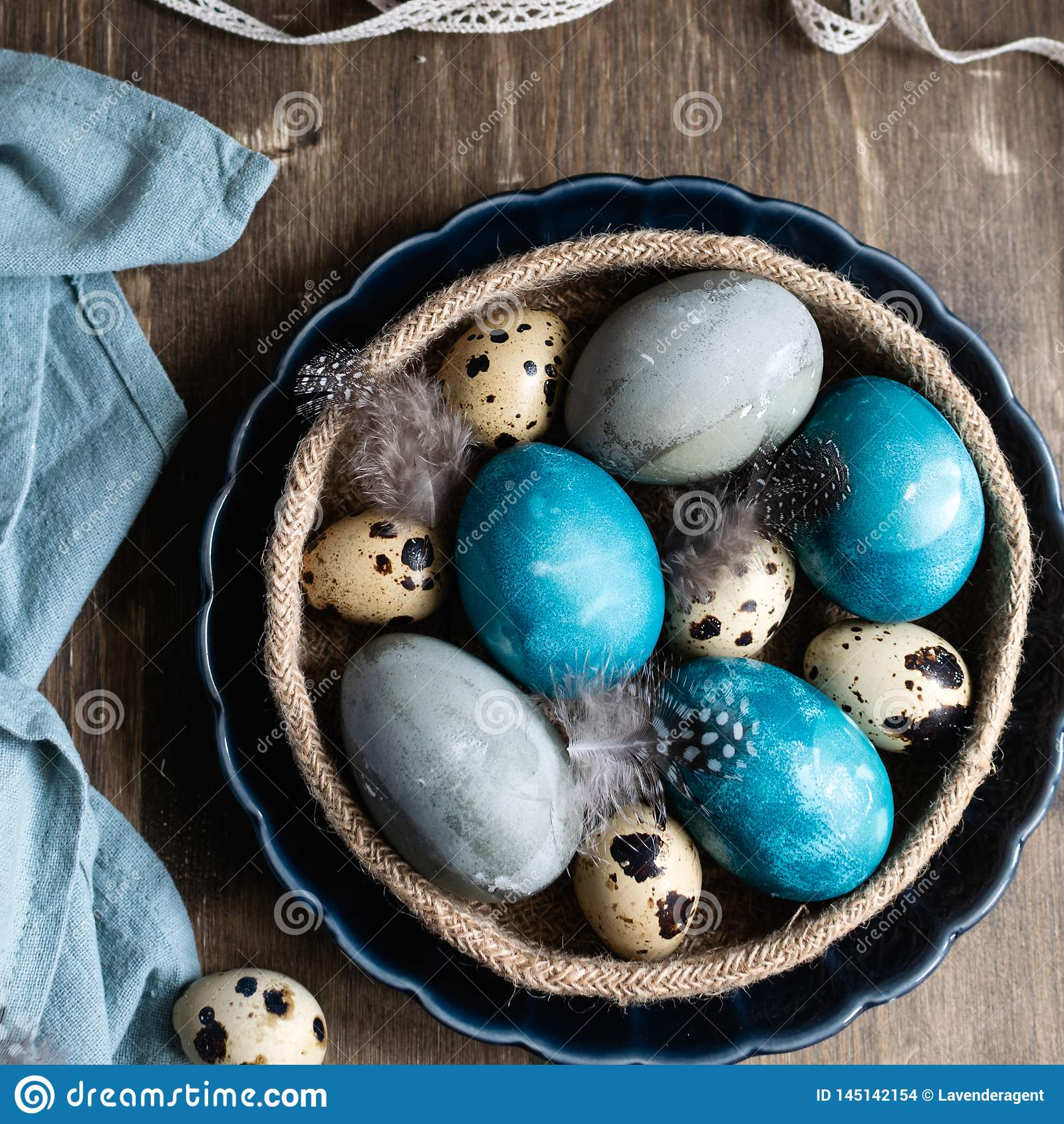 Spring easter concept, - naturally dyed easter eggs, quail eggs, feathers, easter cake, dark wooden background, copy space