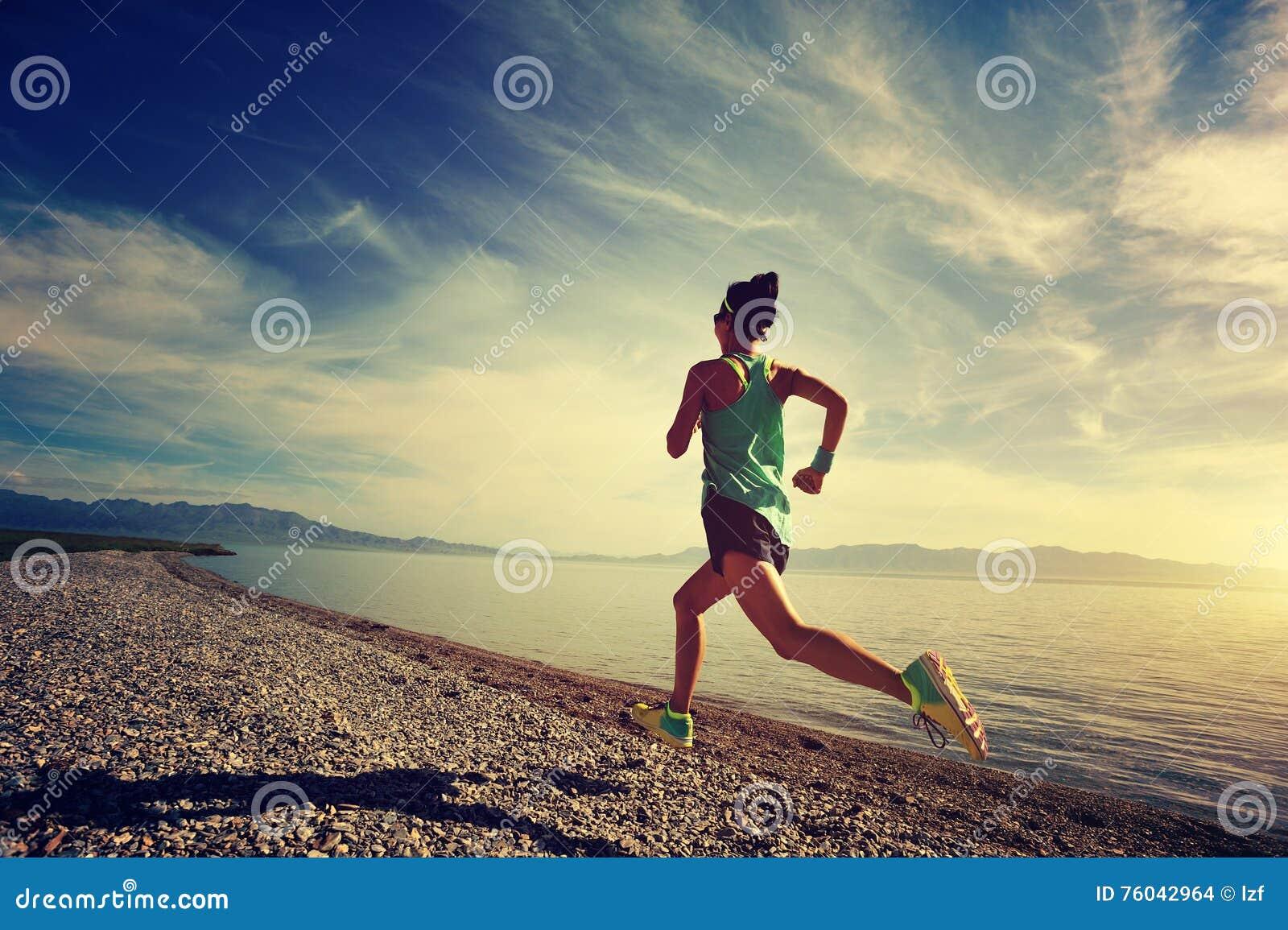 Spring för konditionkvinnalöpare på soluppgångsjösidaslinga