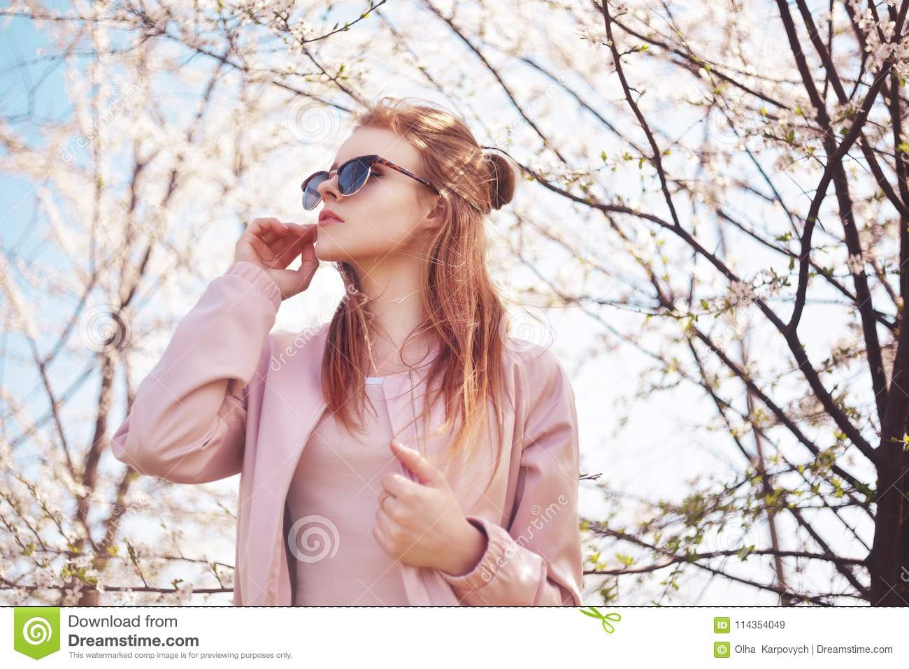 Spring fashion girl outdoors portrait in blooming trees. Beauty Romantic woman in flowers in sunglasses. Sensual Lady.