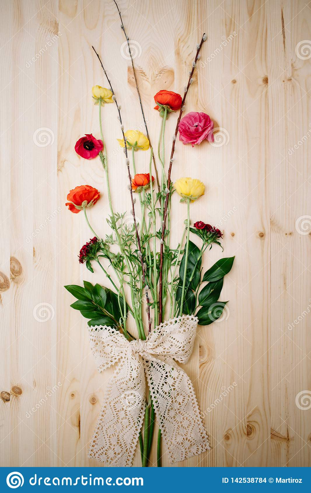 Spring flowers anemones and willow on a wooden background tied with lace ribbon