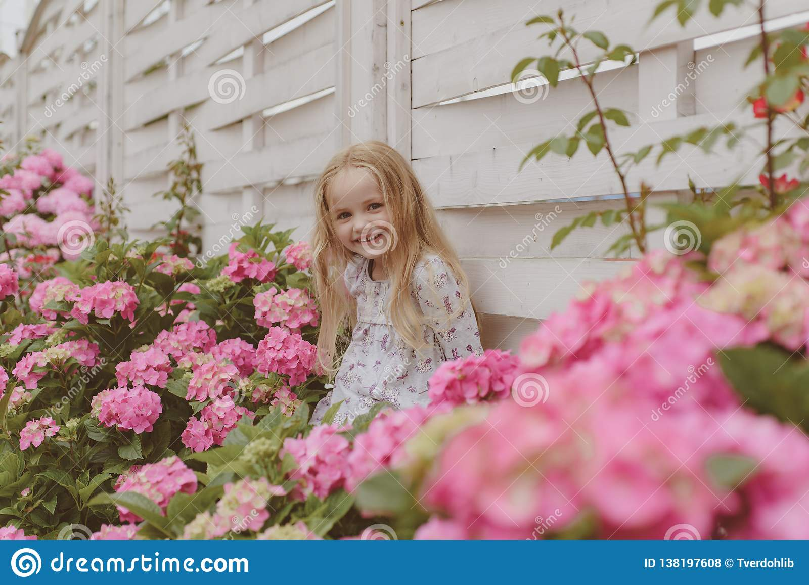 Spring flowers. Childhood. Little girl at blooming flower. Summer. Mothers or womens day. Childrens day. Small baby girl