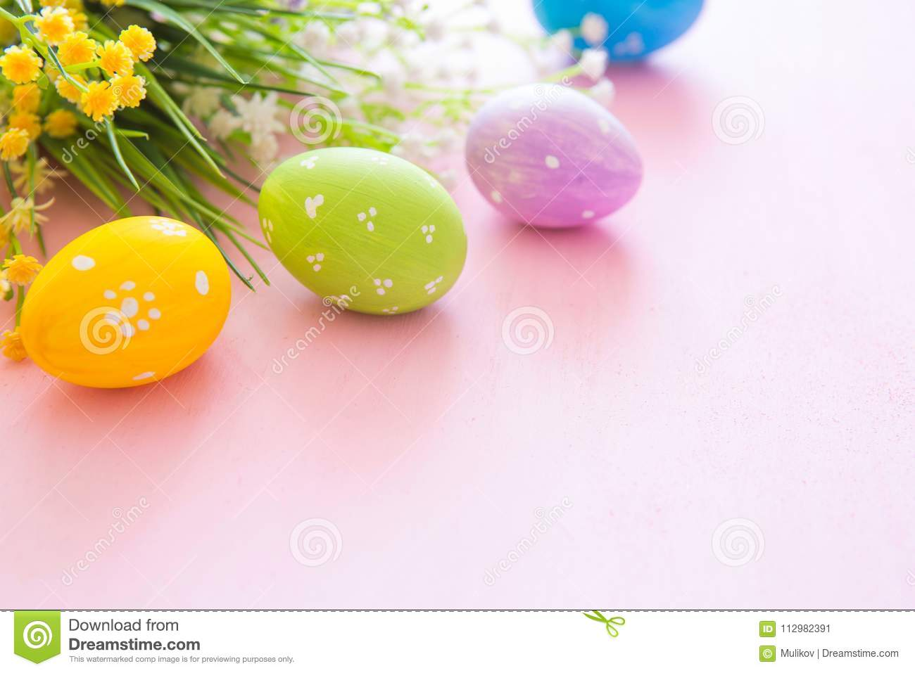 Spring flowers with easter eggs on a pink wooden background