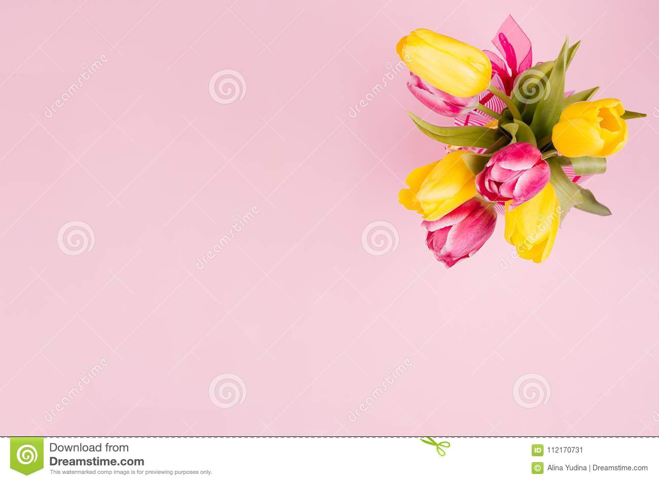 Spring fresh tulips yellow and red bouquet on pastel pink background.
