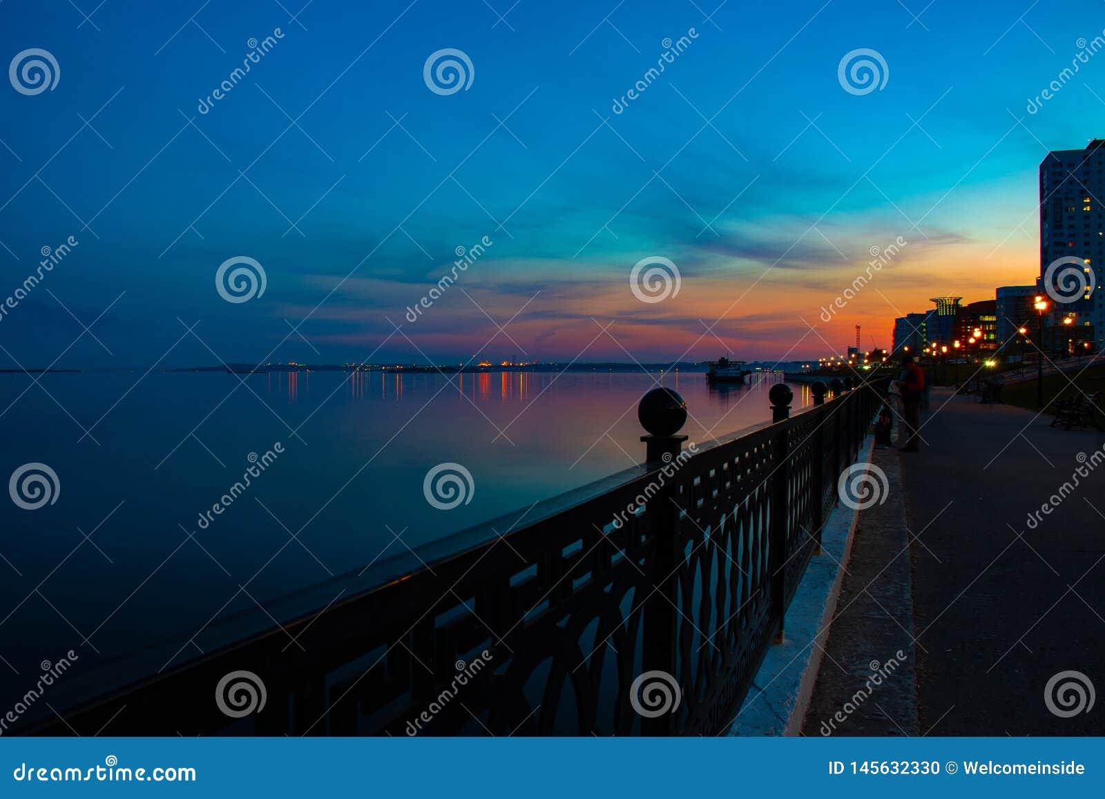 Spring night city Saratov quay under sunset. Street decorative lights and beautiful sky