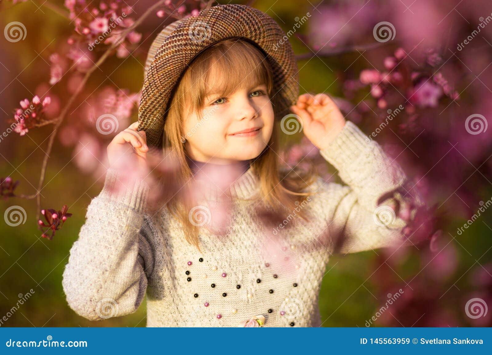 Spring portrait, adorable little girl in hat walk in blossom tree garden on sunset