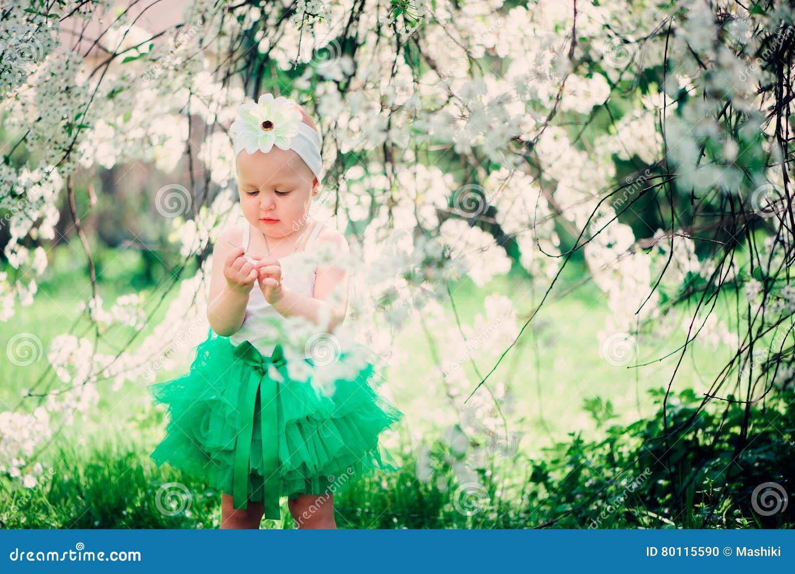 Spring portrait of cute baby girl in green skirt enjoying outdoor walk in blooming garden