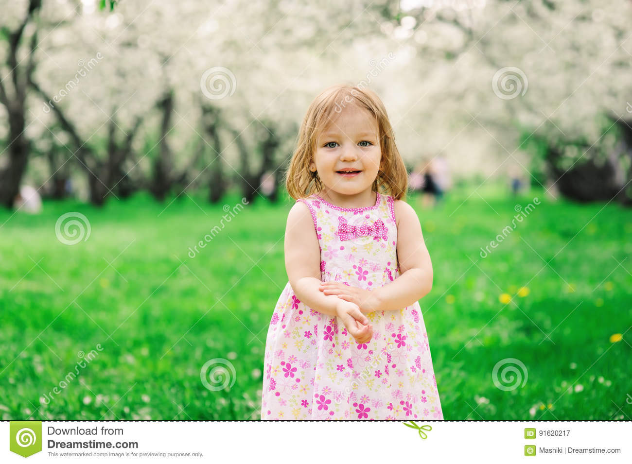 Spring portrait of cute little toddler girl in blue jeans dress walking in blooming park