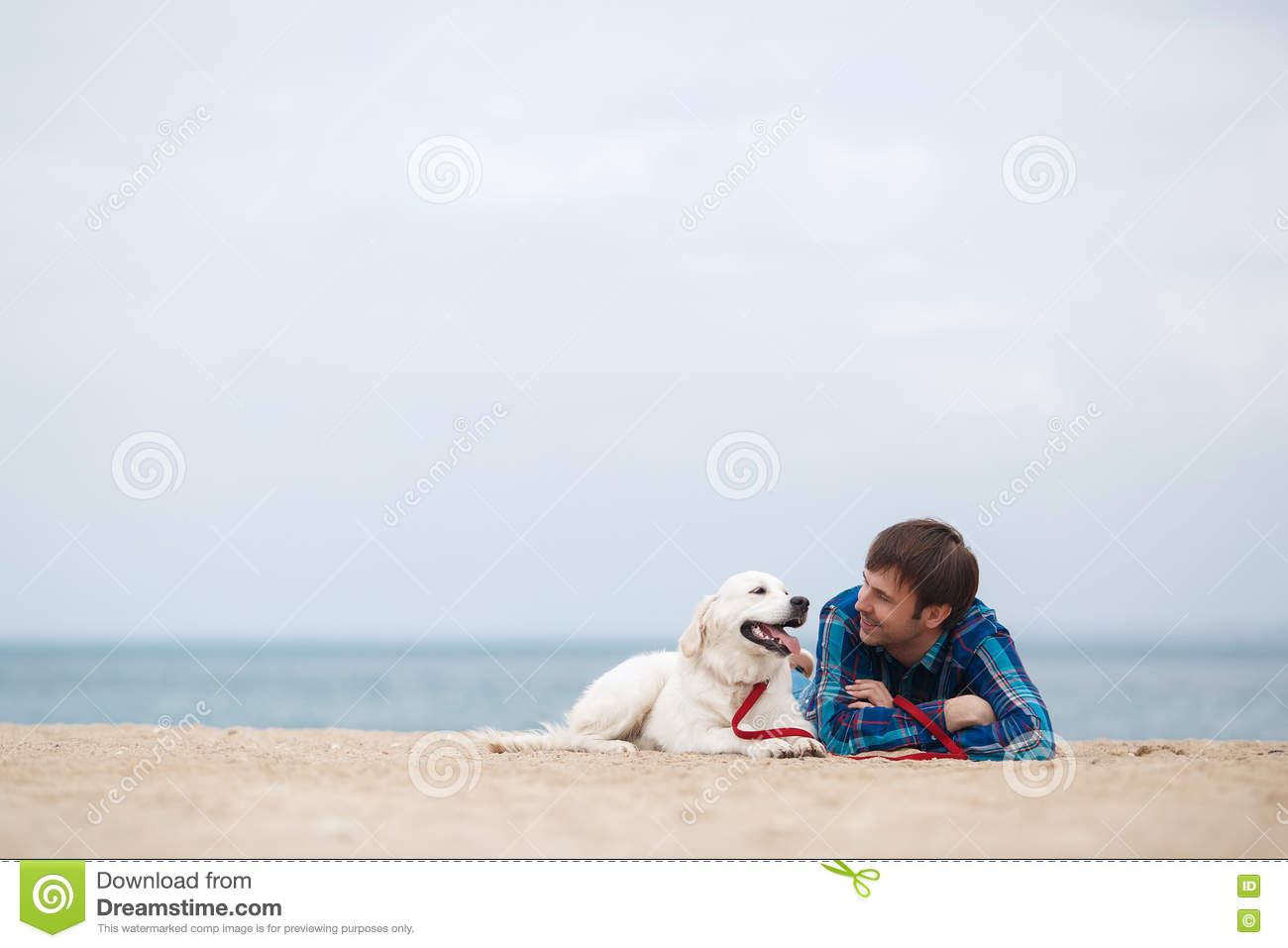 Spring portrait of a young man with a dog on the beach