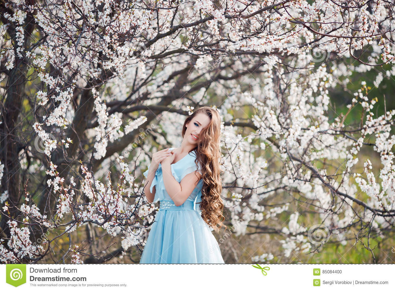 Beauty Girl Outdoors enjoying nature. Beautiful Teenage Model girl with  long healthy blowing hair relaxing in blossom park 5efb56ba1