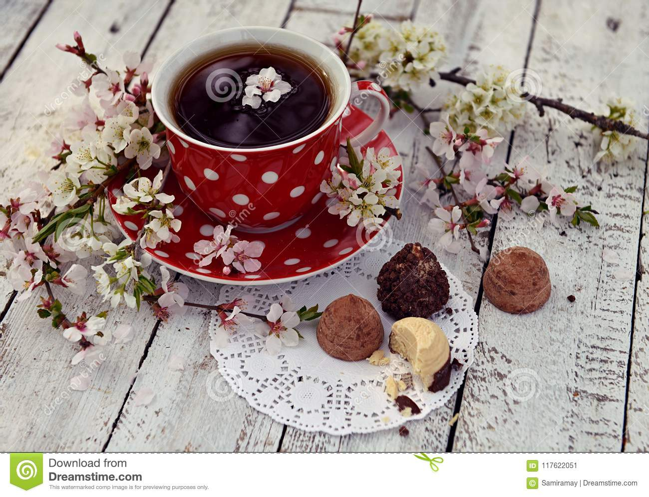 Red Cup Of Tea With Flowers And Chocolates On Planks Stock Image