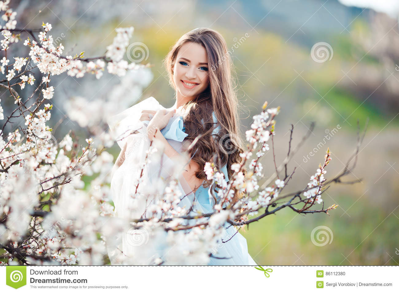 Spring touch. Happy beautiful young smiling woman in blue dress enjoy fresh  flowers and sun light in blossom park at sunset ac9fcf40a