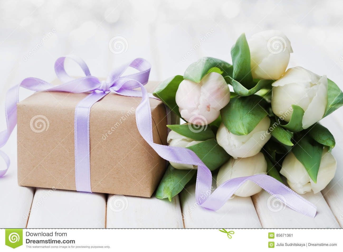 Spring tulip flowers and gift box with bow ribbon on white table. Greeting card for Birthday, Womens or Mothers Day.