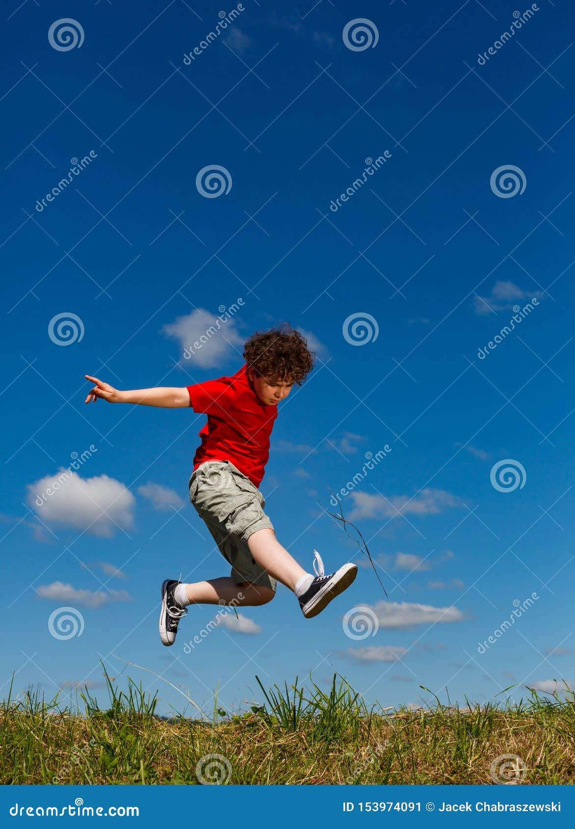 Springen van de jongen, die tegen blauwe hemel loopt